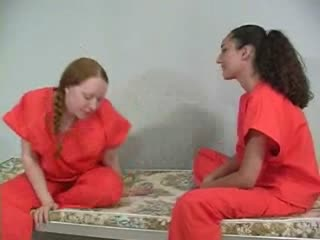 Two bored dykes admire each other's asses in their cell
